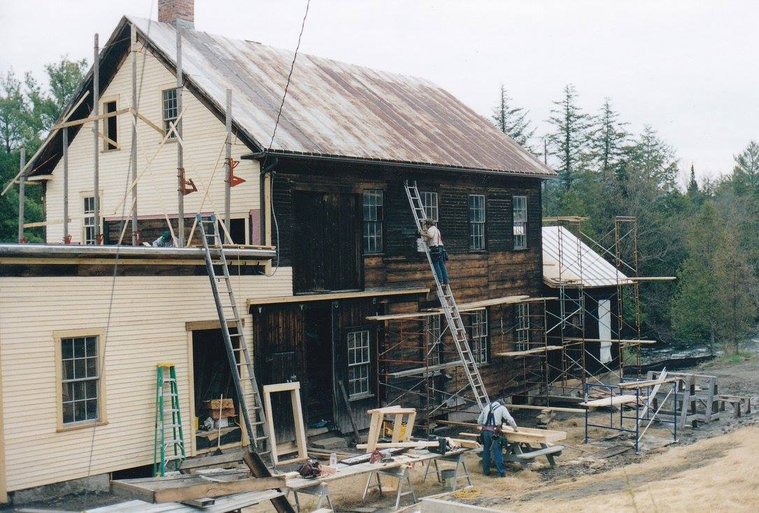 New clapboard siding being added to the mill's exterior by dedicated volunteers.