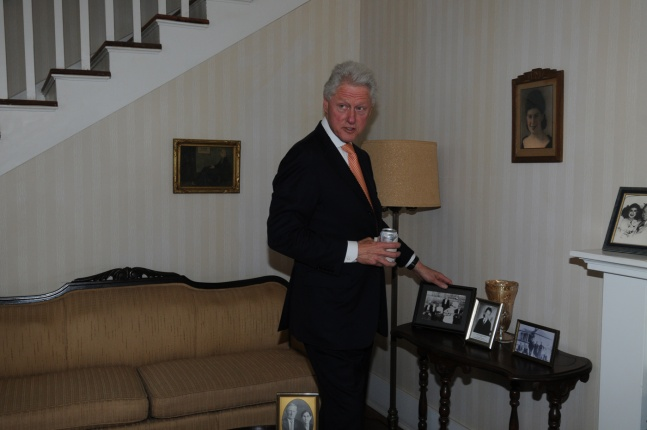 President Clinton Looking at Old Family Photos in the Living Room of the Birthplace Home