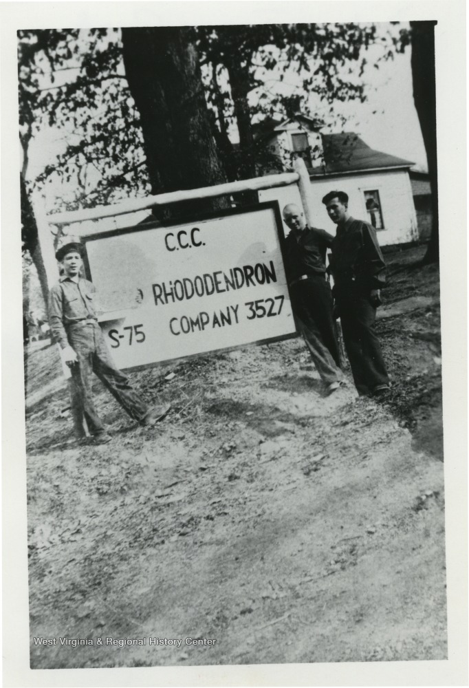 Three Camp Rhododendron members with the camp sign
