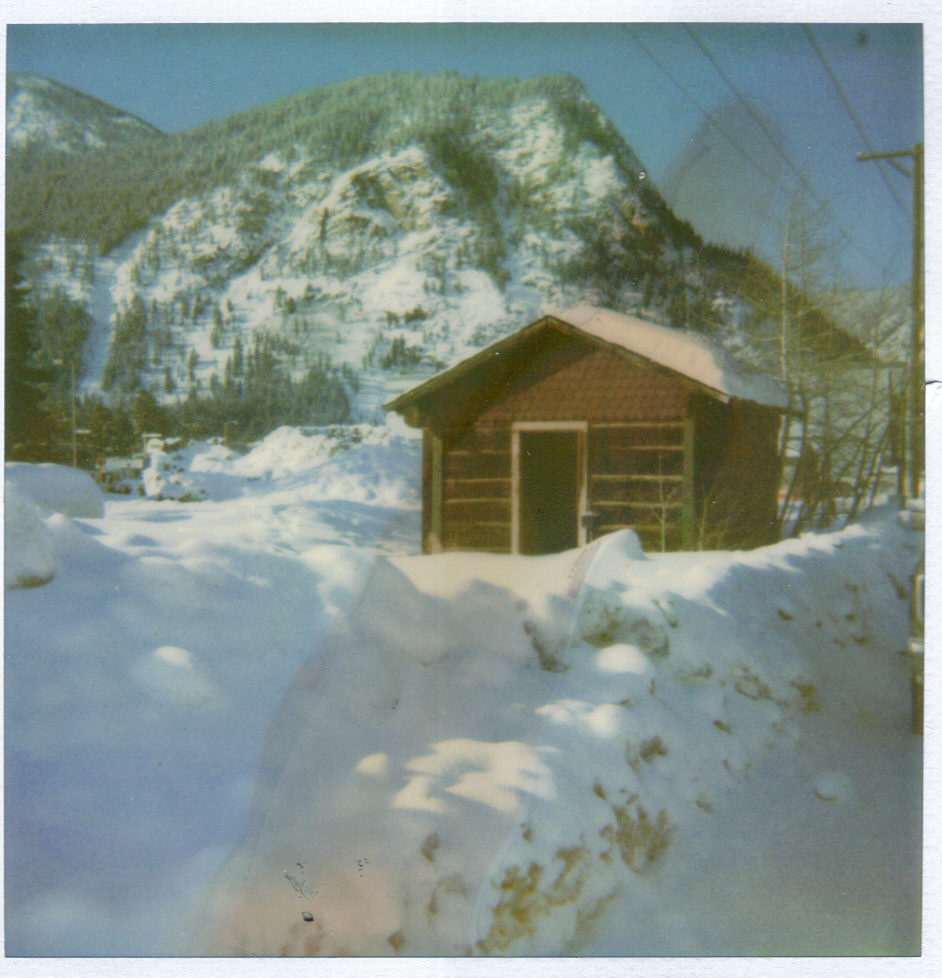 This undated photo depicts the Trapper's Cabin prior to its move to the Frisco Historic Park. You can see Mount Royal in the background and the large drifts of snow in front of the structure.