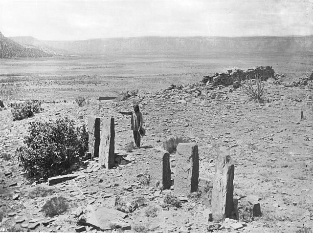 A Zuni man worshipping in front of the Old Zuni stone idols