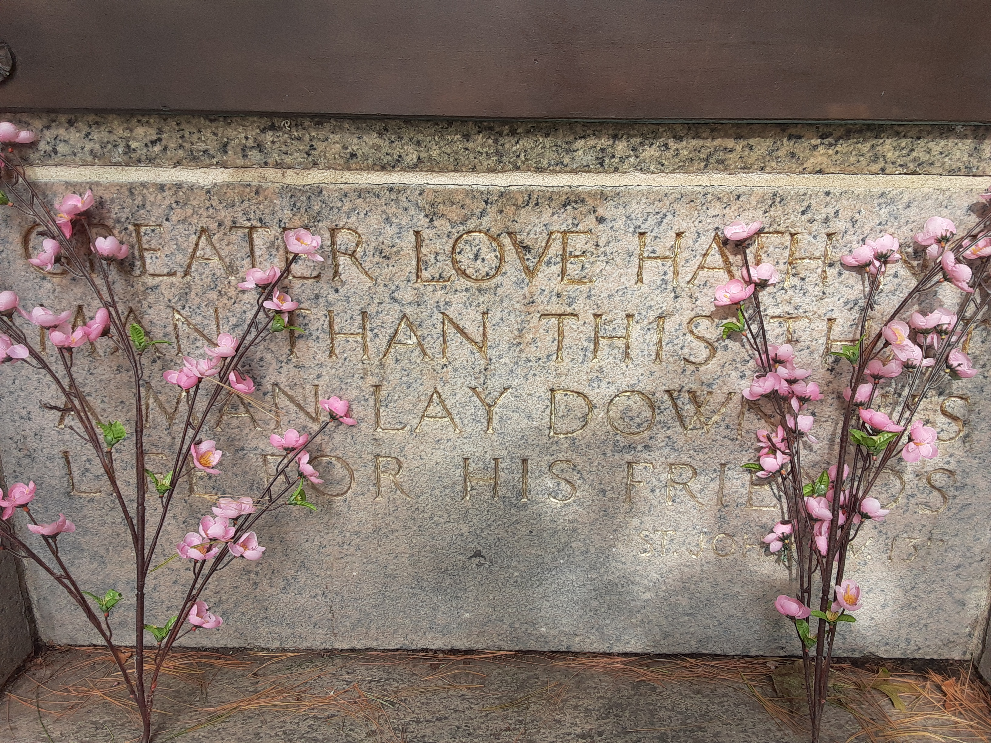 "Directly below the bronze plaque: ""Greater love hath no / man than this that / a man lay down his / life for his friends / St. John XV, 13"""