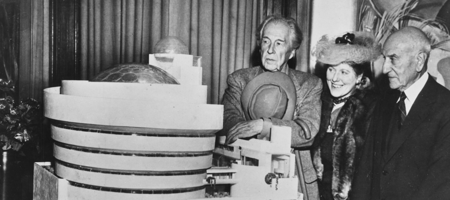 From left to right; Frank Lloyd Wright, Hilla Rebay, and Solomon R. Guggenheim stand with a model of the Guggenheim Museum. Photo taken 1945.