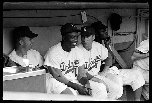 A picture of Jackie Robinson and Pee Wee Reese sitting in the Dodgers dugout during a game