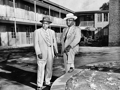 A. G. Gaston (right) stands outside of his motel in 1957.