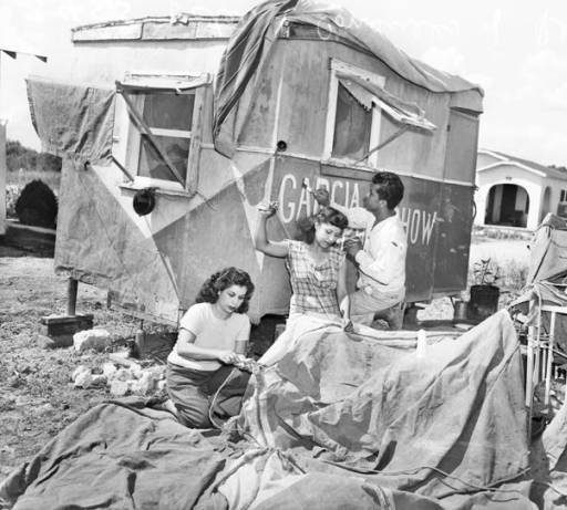 Siblings, Esther, Consuelo, and Raymundo Garcia prepare the tent and caravan for the 1947 season.