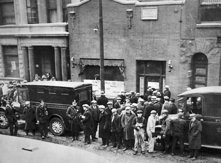 Police and onlookers in front of the SMC Cartage Company following Capone's massacre of rival gang members.