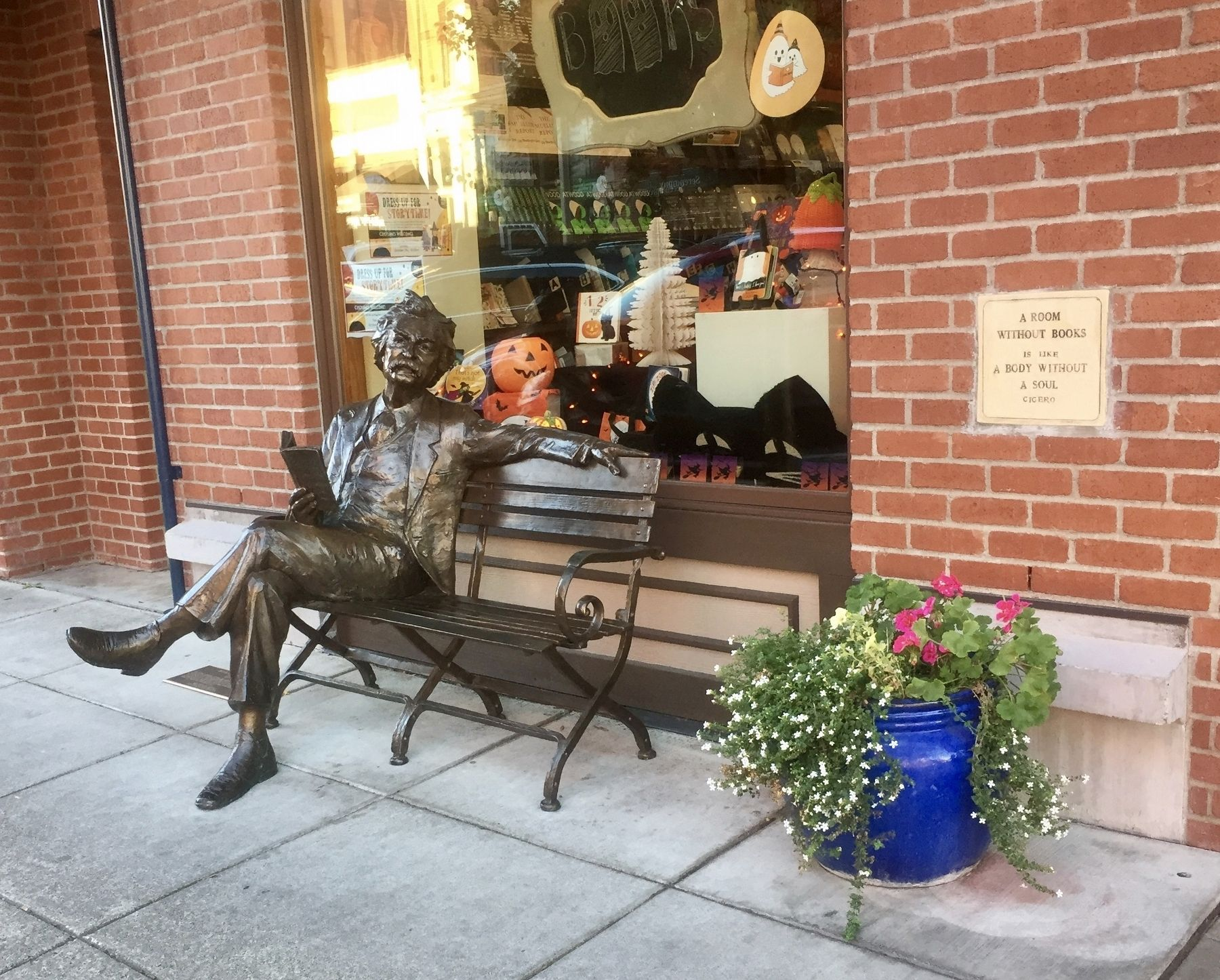 Photograph of the Mark Twain statue and historical marker on the sidewalk next to the bench.