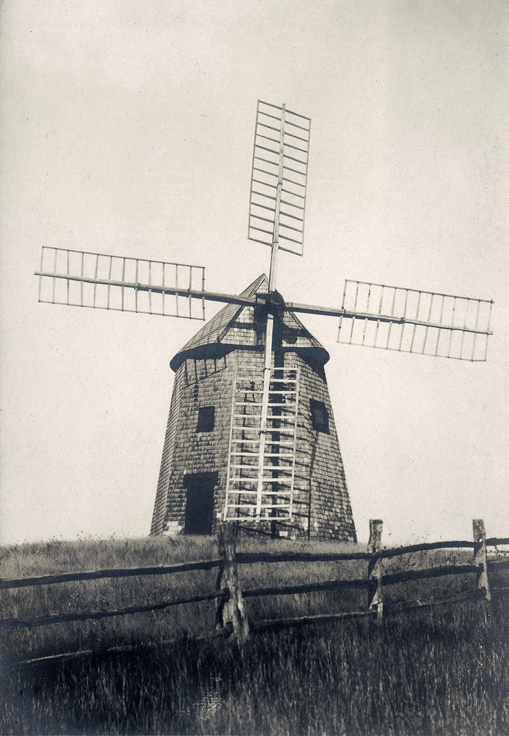 An antique (c. 1905) postcard of the Godfrey Windmill in its original location east of Stage Harbor Road.  This image was taken toward the end of the commercial life of this gristmill.