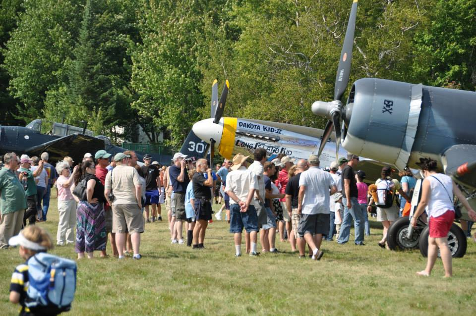 Guests explore visiting WWII aircraft up close and speak with the pilots during open flightline at the 2014 Wings and Wheels Spectacular.