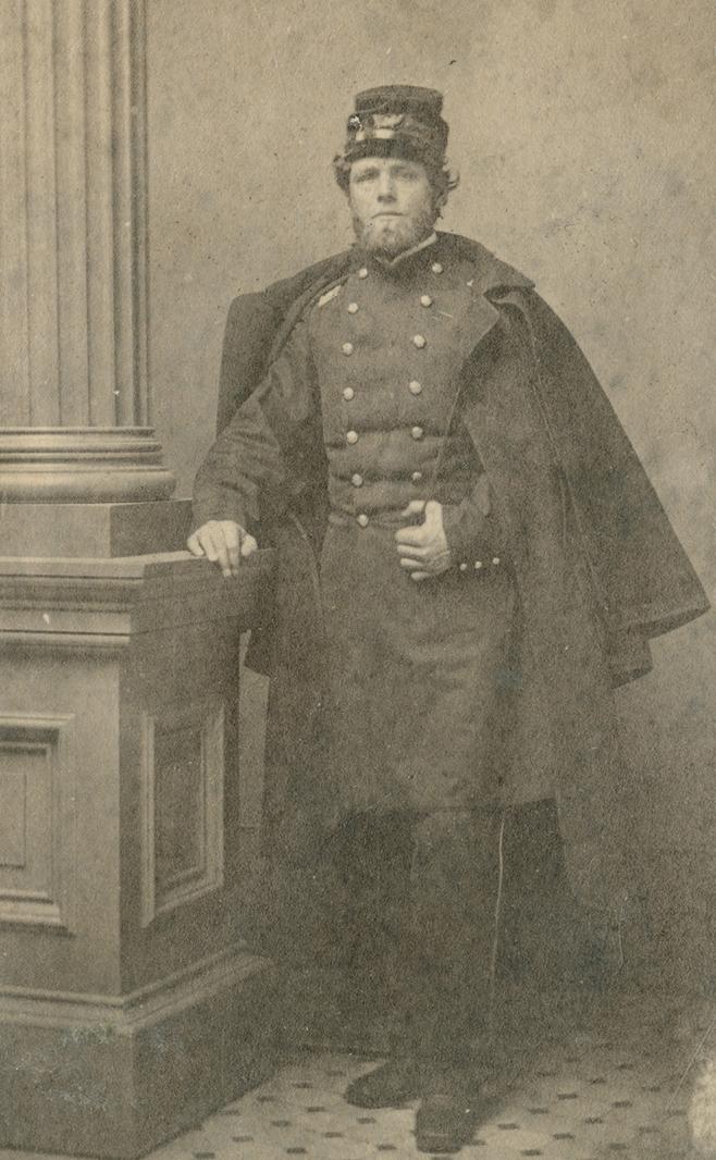 A carte-de-visite, full-length portrait photograph of Cassius Fairchild. He is shown wearing a dress uniform with cap and a cloak.