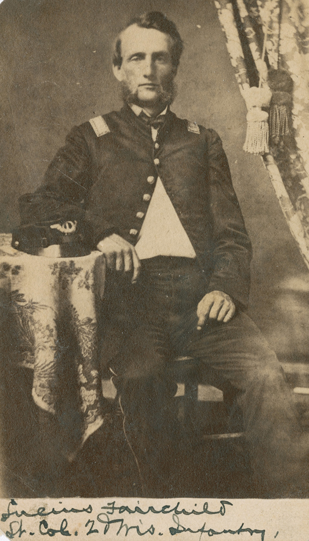 Carte-de-visite full-length portrait photograph of Lucius Fairchild. He is shown seated in uniform with a forage cap resting on a table.