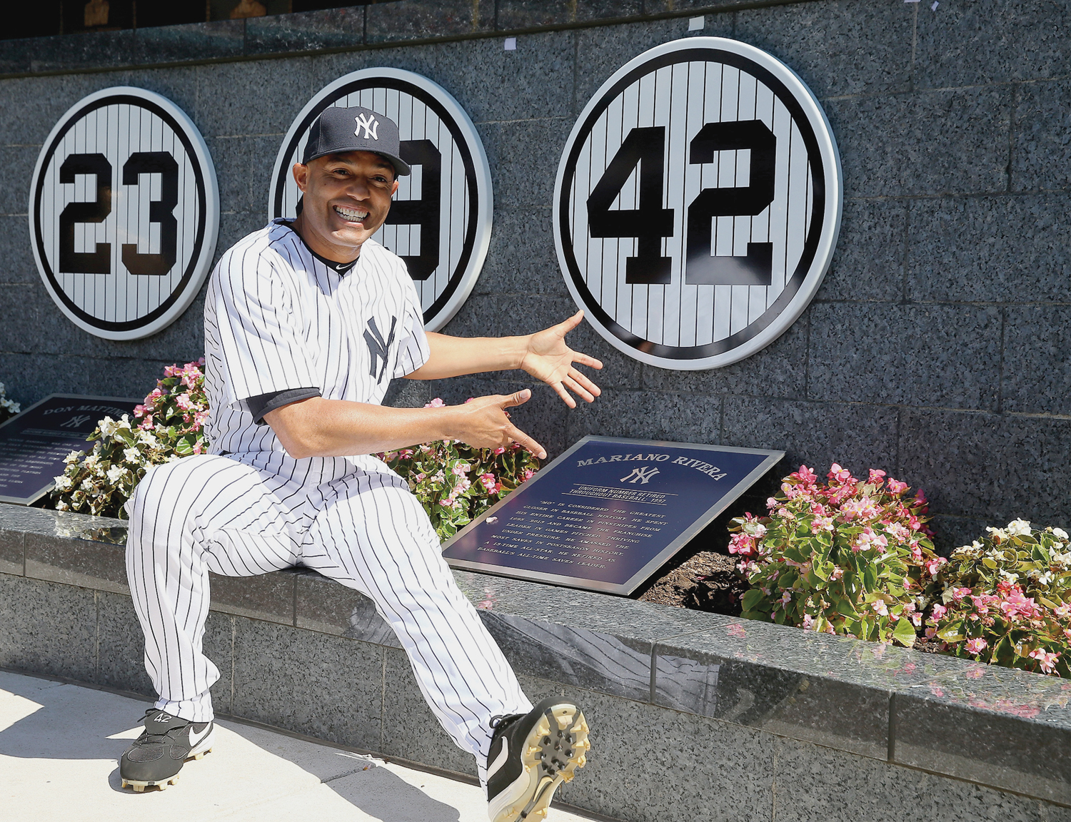 Mariano Rivera sitting next to his retired jersey number at Monument Park.