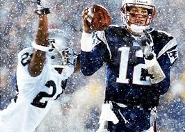 "Tom Brady attempting a pass as an Oakland Raiders defender is about to hit him.  This is the play that led to the game being known as ""The Tuck Rule Game""."