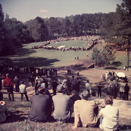 """Patrons watch Tournament play on the 6th green."" (1961) Photo courtesy of http://www.masters.com/en_US/discover/timeline.html."