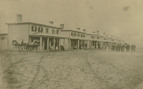 This photograph shows the 5th Infantry Band parading on the streets of Fort Hays, Kansas, in front of the officer's quarters.