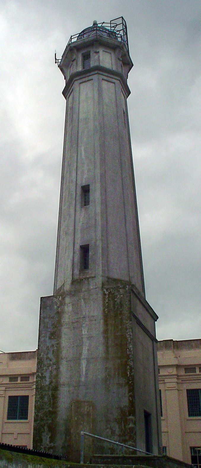 """The lighthouse tower adjacent to the prison cell house.   """"Alcatraz Island Lighthouse Tower"""" by Centpacrr (Digital image), Licensed under CC BY-SA 3.0 via Wikipedia."""