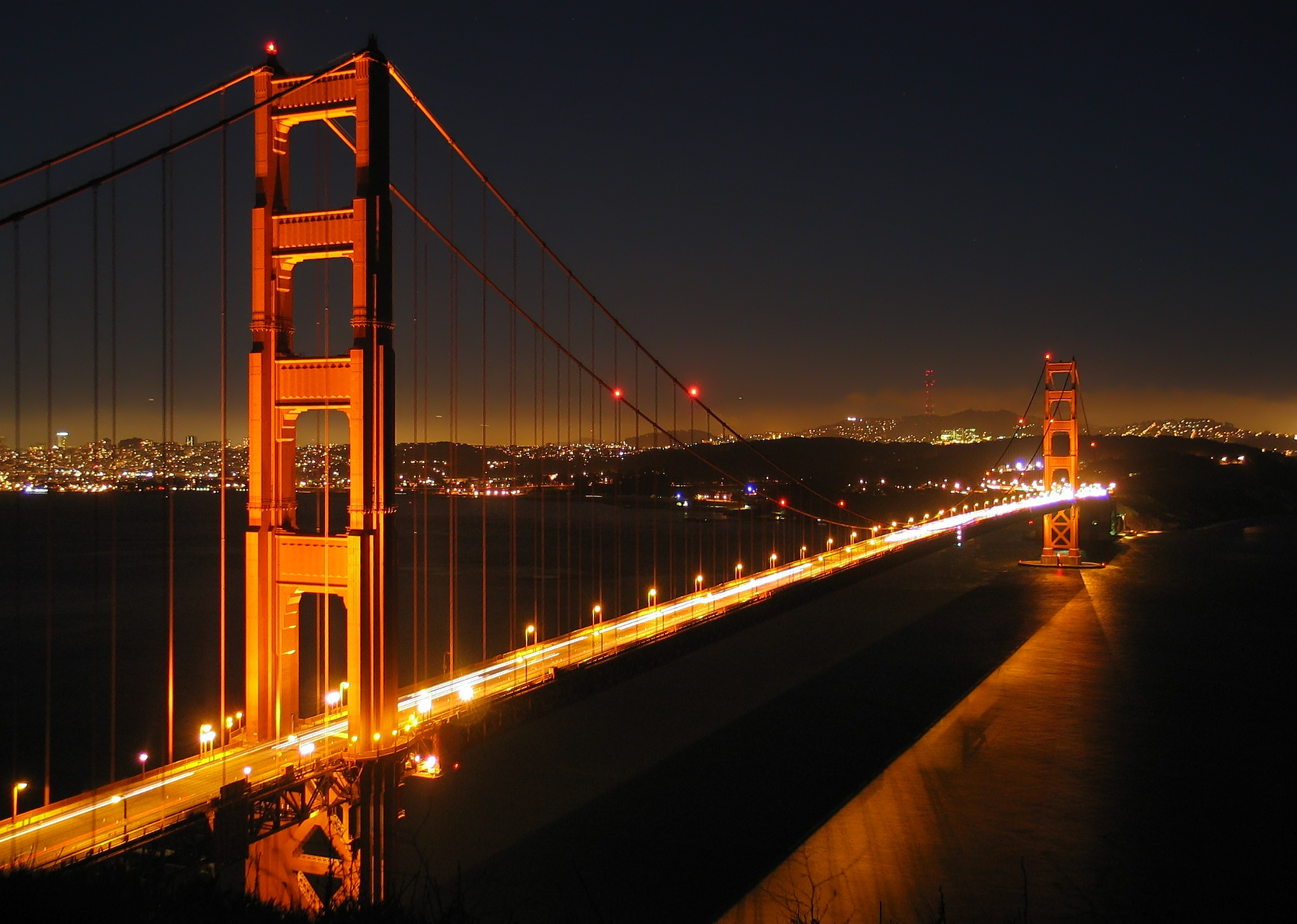 """The Golden Gate Bridge by night, with part of downtown San Francisco.   """"Ggb by night"""" by Daniel Schwen. Licensed under CC BY-SA 3.0 via Wikimedia Commons."""