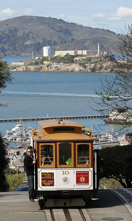 "San Francisco cable car number 10 heading south on Hyde St, crossing Chestnut St, with Hyde St Pier and Alcatraz Island in the background. ""10 Cable Car on Hyde St"" by jjron. Licensed under GFDL 1.2 via Wikimedia Commons ."