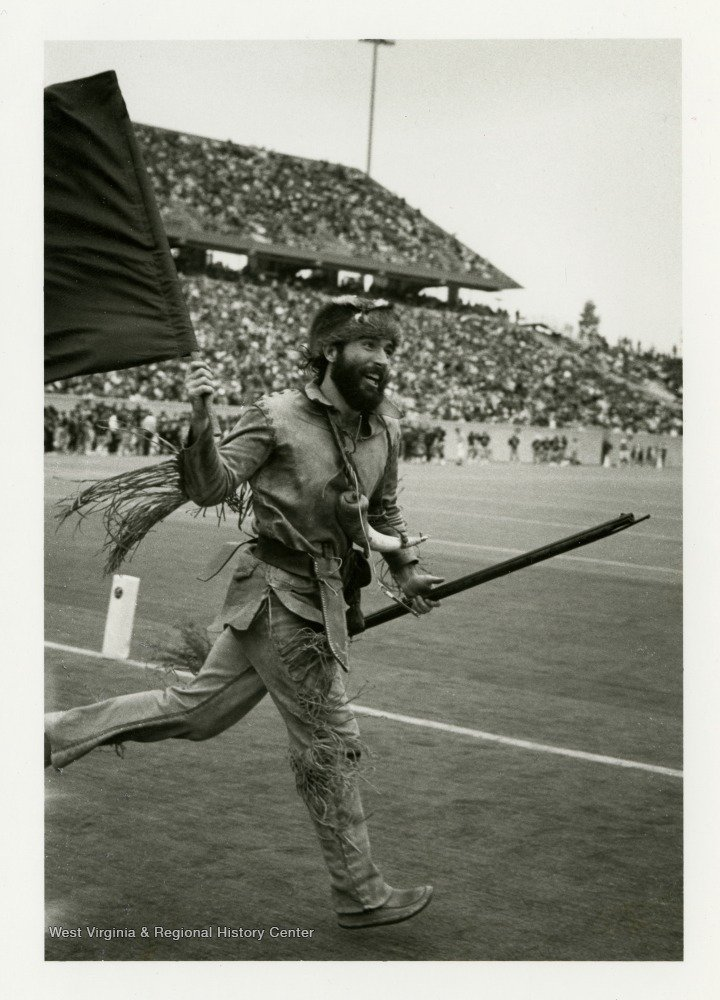 "Official Mountaineer mascot Matthew Zervos carries WVU's colors onto the ""new"" Mountaineer Field, which was then over half a decade old during Zervos's tenure in 1986-1987. West Virginia & Regional History Center."