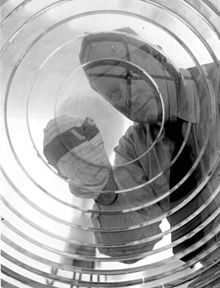 Lighthouse keeper, part of the Coast Guard, cleans the lens. Circa 1960s.