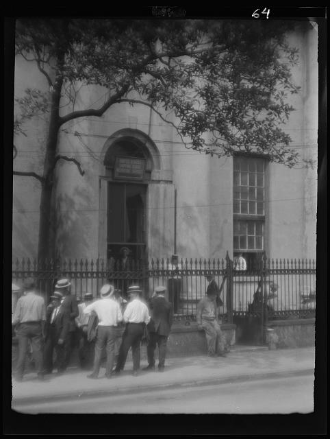 Men standing in front of the bank sometime between 1920 and 1926.