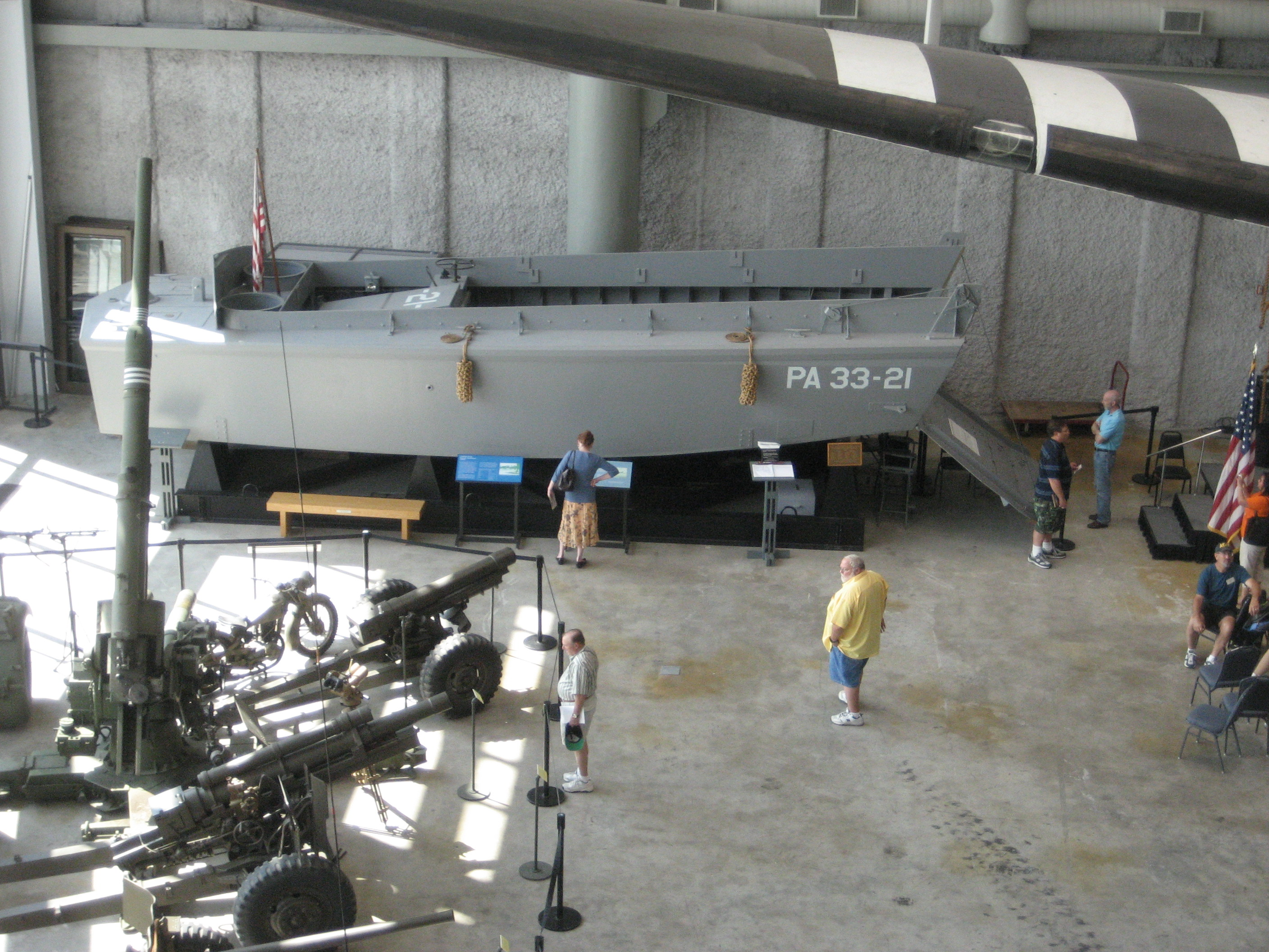 A Higgins Boat and various pieces of artillery on display.
