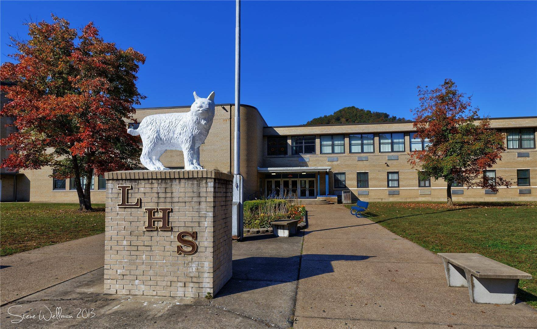 In front of the school, sits the statue of the wildcat. The wildcat serves as the mascot of Logan High School. The lettering underneath shows the colors of the school - blue and gold. 