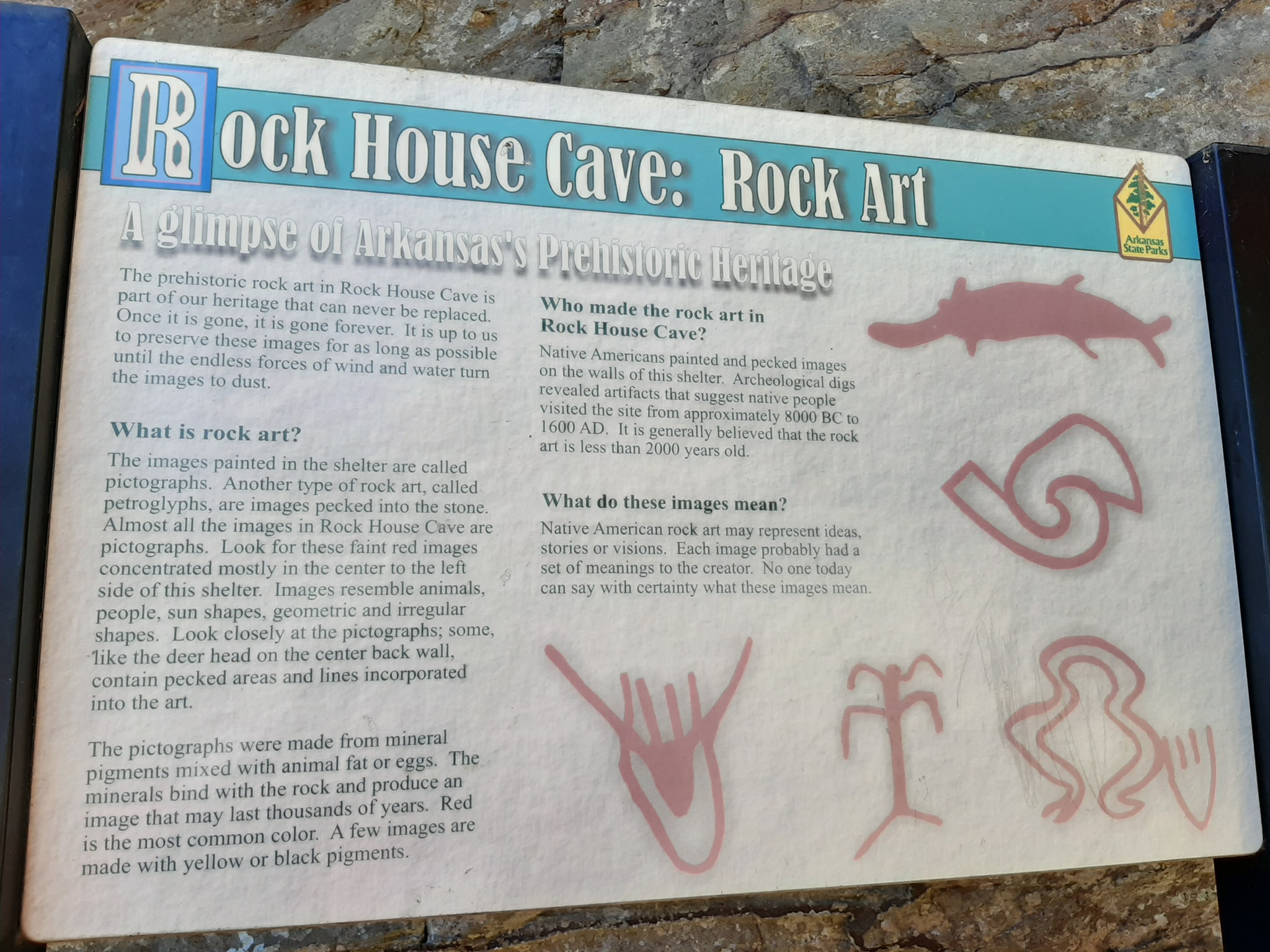 A sign near the entrance at Rock House Cave at Petit Jean State Park in Arkansas displays some of the rock art that can be found inside the bluff dwelling.