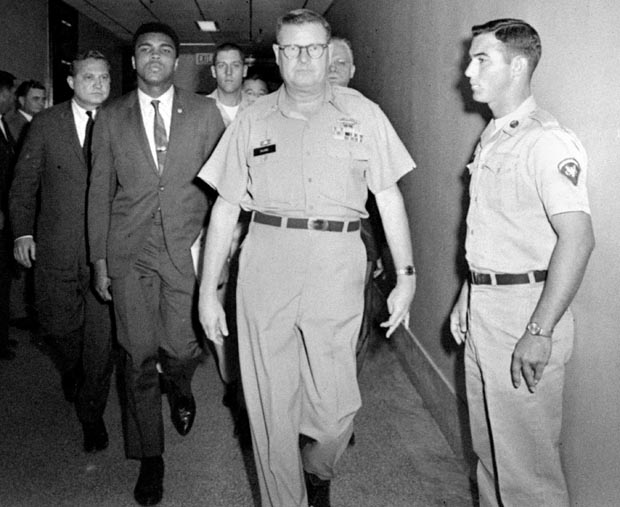 Heavyweight champion Muhammad Ali is pictured being escorted from the Armed Forces Examining and Entrance Station in Houston, Texas, April 28, 1967, by Lt. Col. J. Edwin McKee, commandant of the station, after Ali refused Army induction.