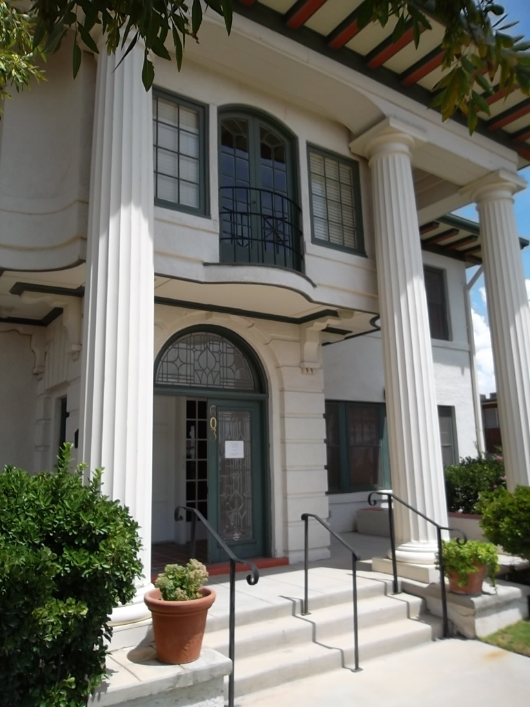 The Classical Revival style house features four large columns in the front supporting the roof.