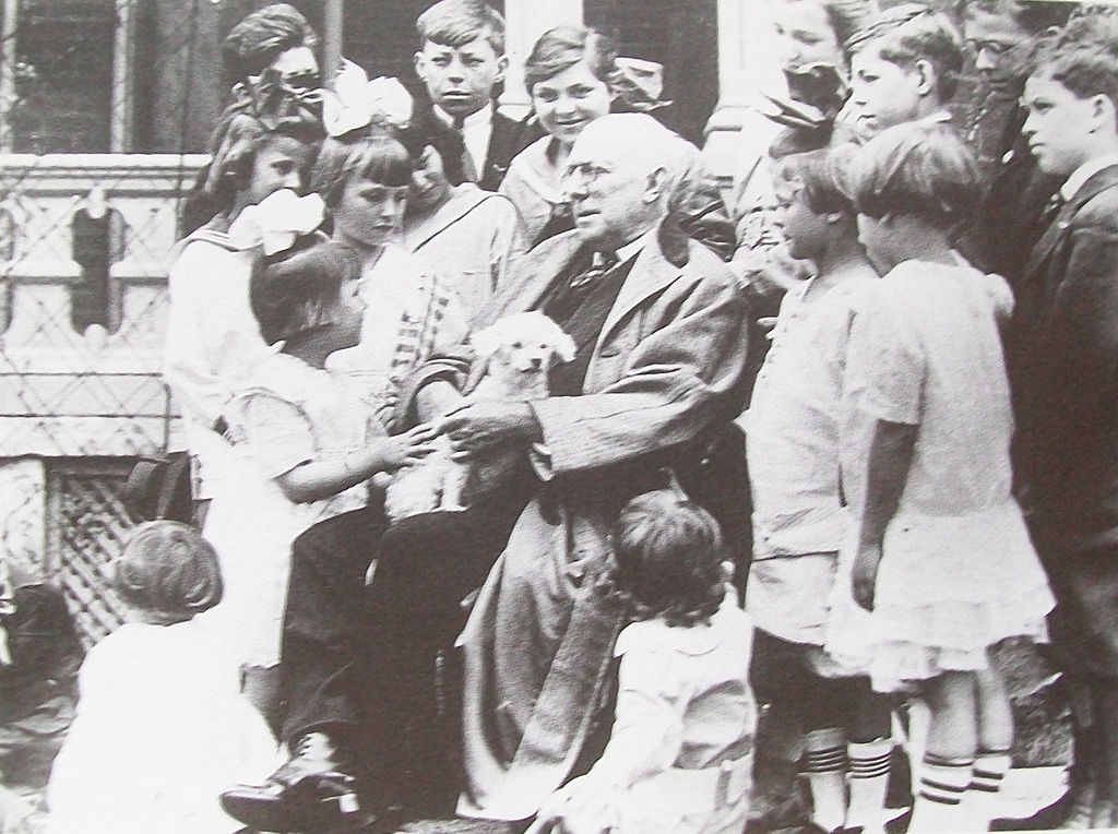 James Whitcomb Riley holds his pet dog while posing for a photo with a group of children in front of his Indianapolis home in 1916. Courtesy of the State of Indiana.