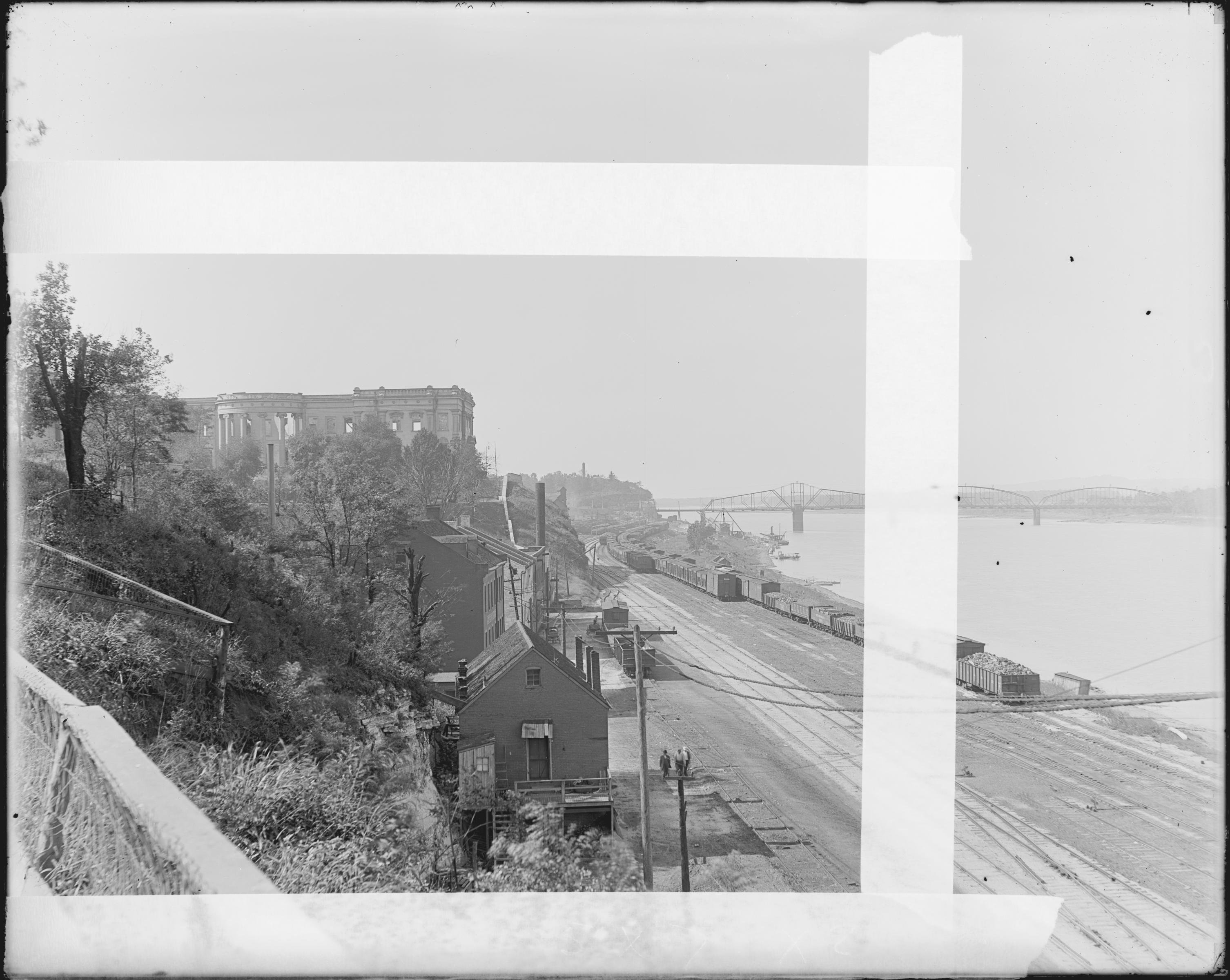 Glass plate negative taken in 1911 looking west toward the ruins of the old Mo. State Capitol.  Also shows the buildings which now constitute Jefferson Landing State Historic Site, in the foreground. Courtesy Missouri State Museum.