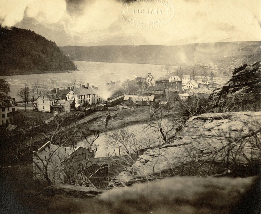 This photograph shows an 1864 view of Harpers Ferry from Jefferson Rock. A train carrying Union soldiers passes across Virginius Island. Courtesy of Crossroads of War.