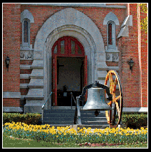 Church Main Entrance and Bell Photo with spring Daffodil flowers in the background, provided by Bob Neill, Church Member.