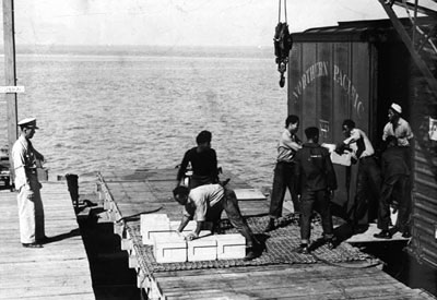 A white officer supervises African American enlisted men as they load munitions onto a vessel at Port Chicago.