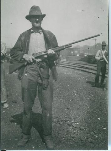 A white man poses with his rifle during the riot. He may have been part of the mob, or he may have been part of the deputized police force raised among the city's white male population.