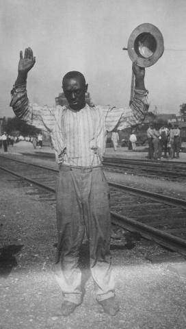 An unarmed black resident of the city surrenders to police during the event known as the Tulsa Race Riot.