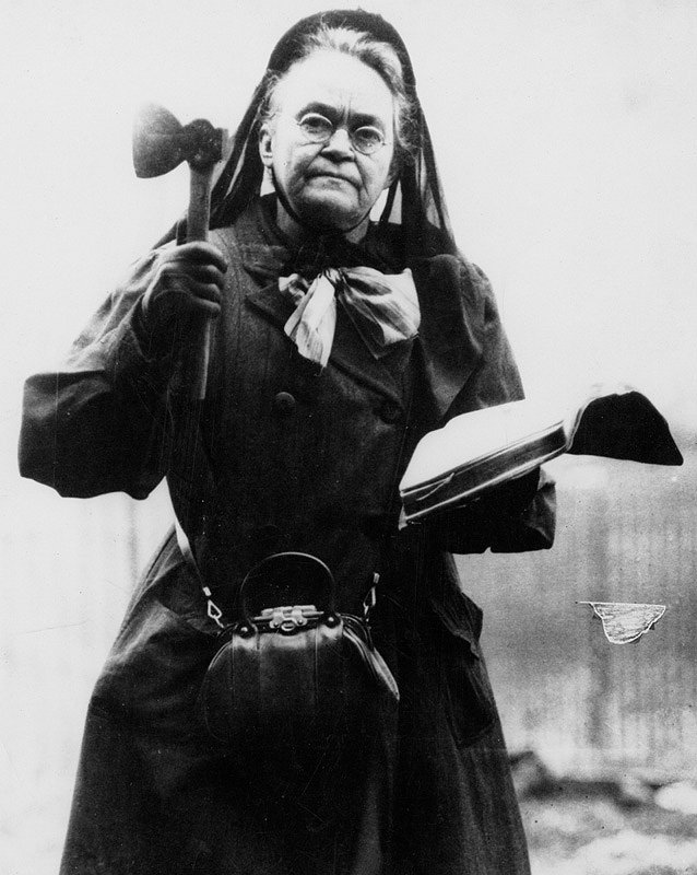 Carrie A. Nation in 1910, holding one of her hatchets in one hand and the Bible in another, a fitting depiction of her preference for virtue and the willingness to use violence if necessary to procure it.