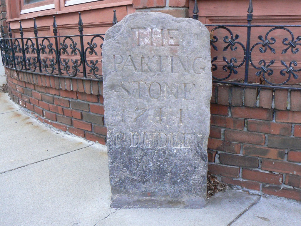 "The ""Parting Ways"" Stone (erected 1741), part of the 1767 Milestones in Massachusetts. The stone is located in the Roxbury section of Boston. Image by User:Magicpiano. Licensed under GFDL via Wikimedia Commons."