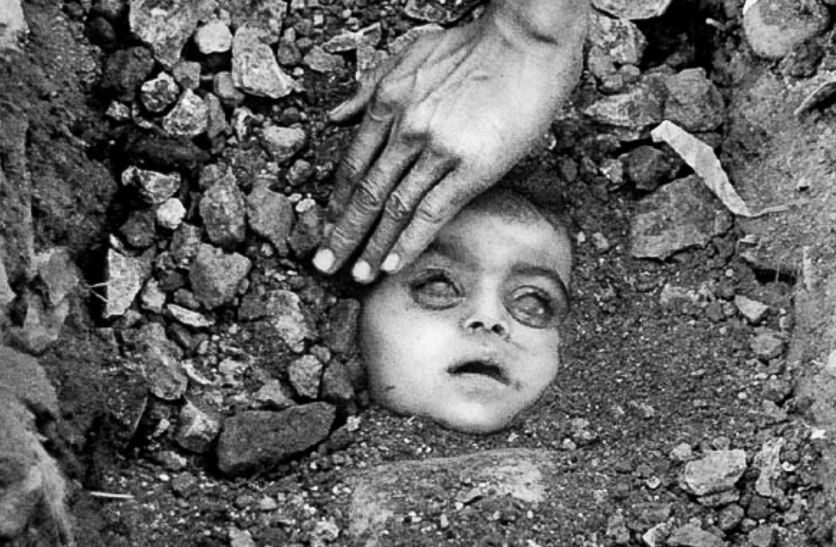 The face of a freshly buried child in Bhopal, India, victim of Carbide's disastrous chemical spill in 1984. Over 25,000 people died from direct effects of the fatal chemicals, and 150,000 continue to suffer health problems. Photo by Raghu Rai.