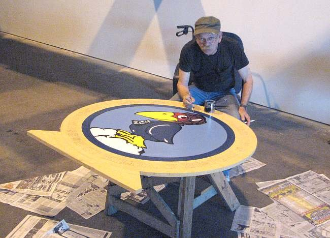 Jerry Blair, founder of the Kansas Museum of Military History, painting the museum's new logo.