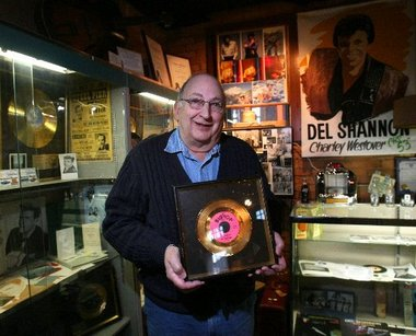 Curator holding a Del Shannon gold record.