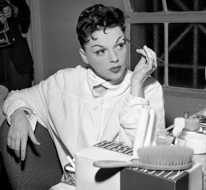 Judy Garland applying makeup backstage at the Greek Theater in 1957.