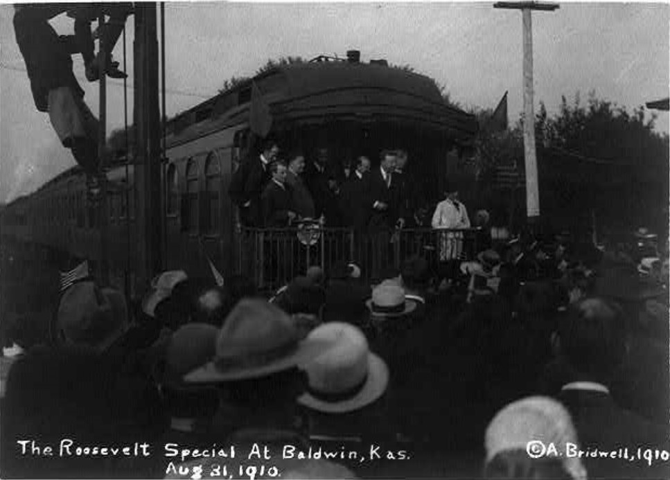 1910 photograph of Teddy Roosevelt speaking from back of The Roosevelt Special at the Baldwin City Depot (Library of Congress)