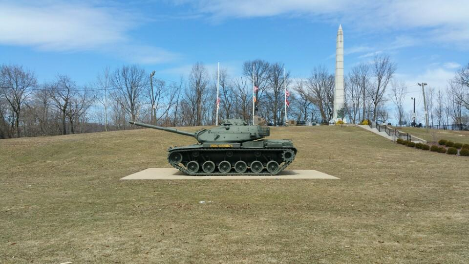 The memorial park includes several monuments and a static display of a tank. The memorial on the hill includes several plaques that honor veterans of multiple wars and conflicts.