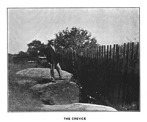 Sidney Perley standing at the crevice near Proctor's Ledge where the bodies of those executed were thrown