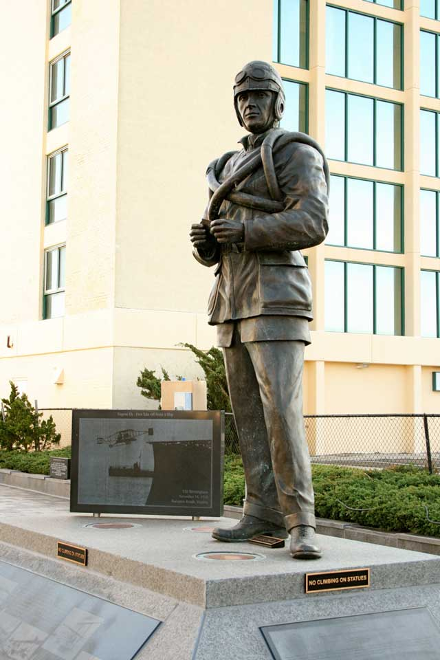 Bronze statue of Eugene Ely, the first pilot to fly a plane off of a ship deck.