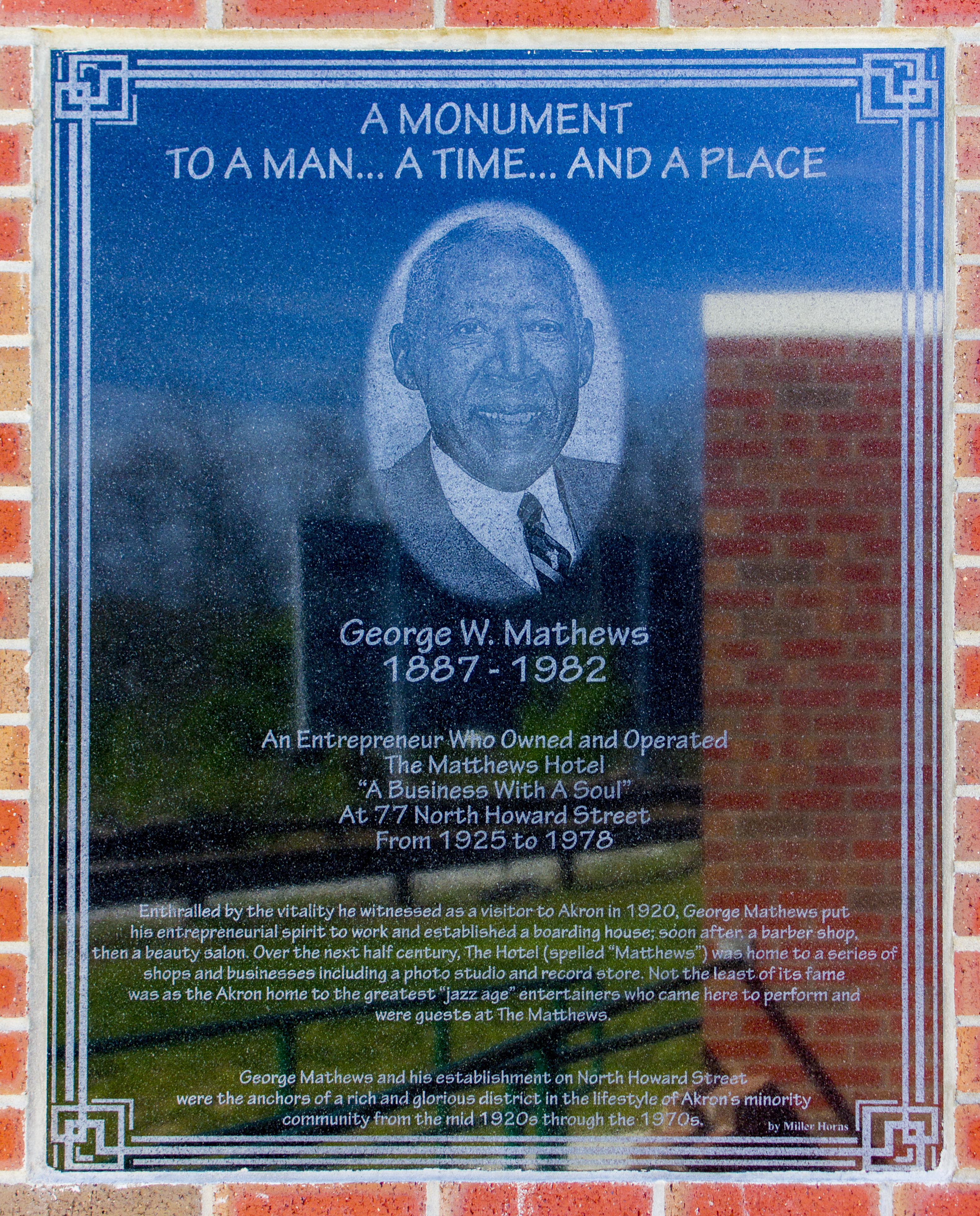 A modest plaque honoring the accomplishments of George W. Mathews, a business leader in the Howard Street district.