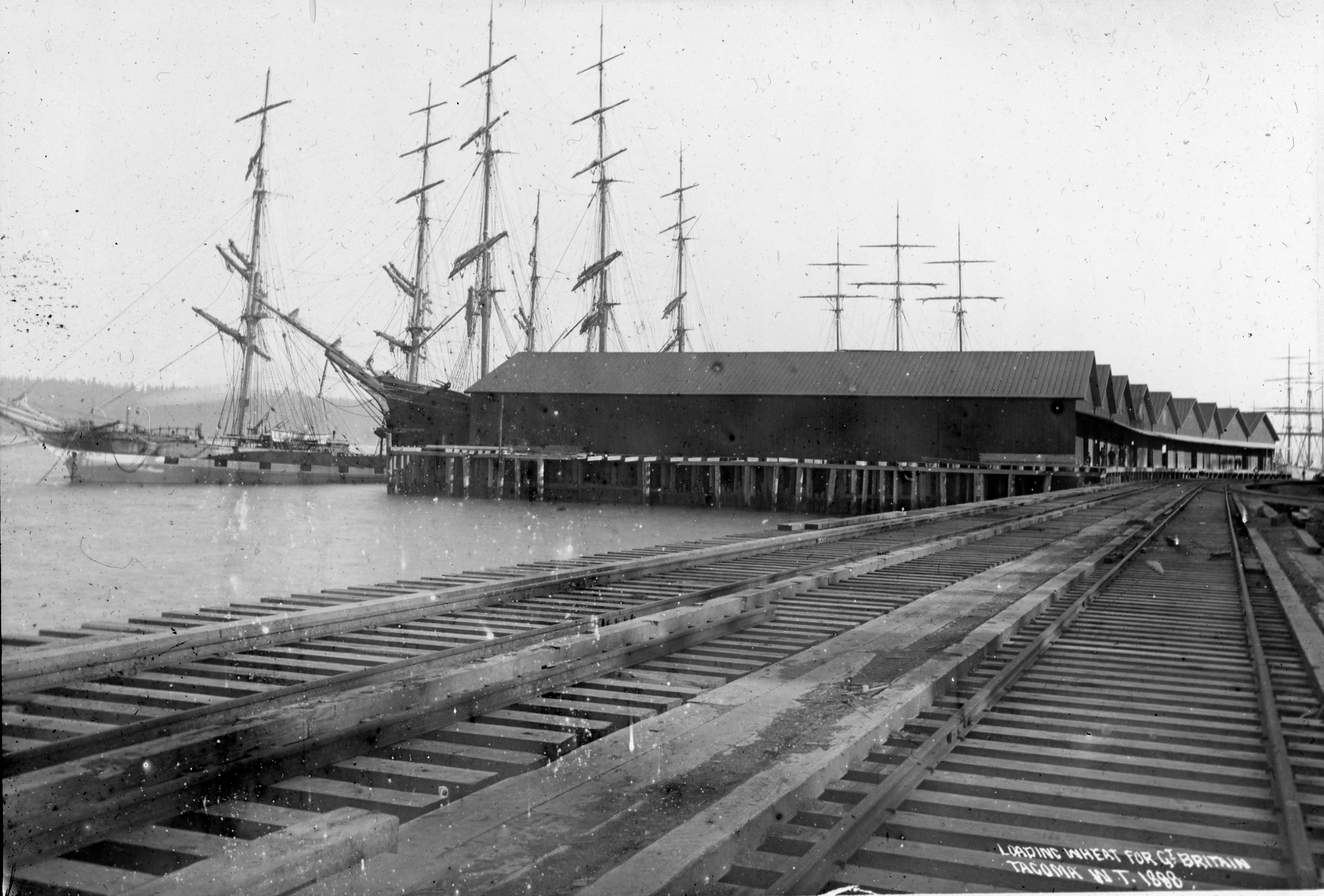 Northern Pacific Railroad tracks past grain warehouses and the ships that kept them full of product.